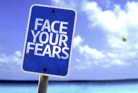 Face Your Fears sign with a beach on background